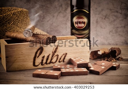 Cigar and Rum. Cigar with smoke. Cigar and cognac from Cuba. Cigar and domino play. Cigar still life. - stock photo