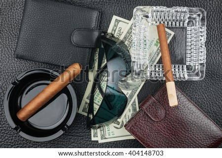 Cigar, ashtray, sunglasses, money, purse, on genuine leather, can be used as background - stock photo