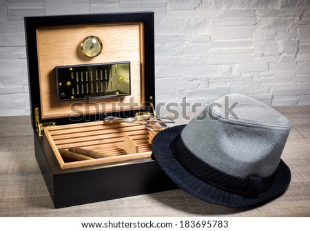 Cigar humidor, vintage luxe cigar box and scissors on a wood table and white brick wall background - stock photo