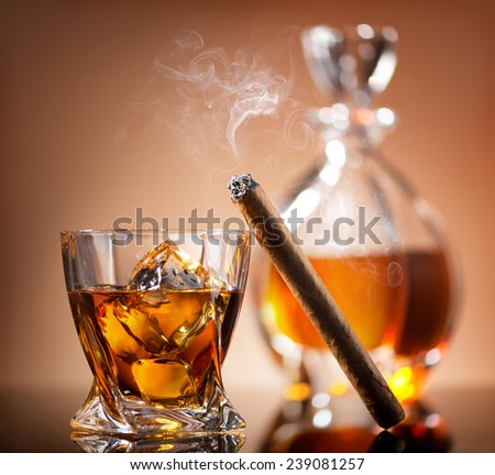Cigar on glass of whiskey with ice cubes - stock photo