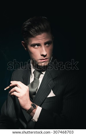 Cigar smoking retro 40s businessman in suit and tie. Hair combed back. Against dark background. - stock photo