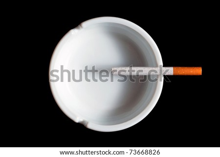 Cigarette ashtray in white on a black background - stock photo