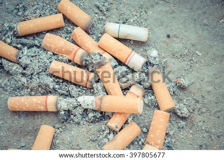 Cigarette burning in outdoors ashtray with sand closeup - stock photo