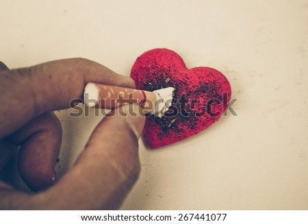 Cigarette burnt a red heart - smoking destroying health concept - stock photo