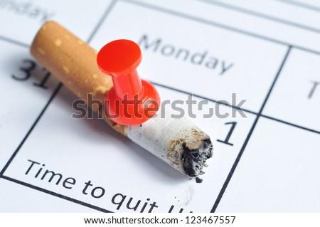Cigarette butt impaled on calendar - stock photo