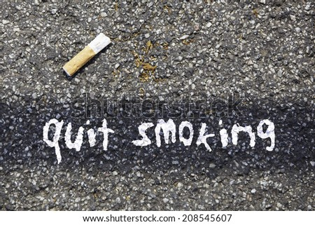 cigarette butt on a tar road with the written massage: quit smoking - stock photo