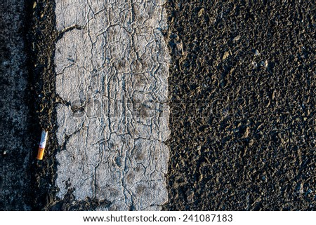 cigarette butt on a tar roads,cut down on my cigarette - stock photo