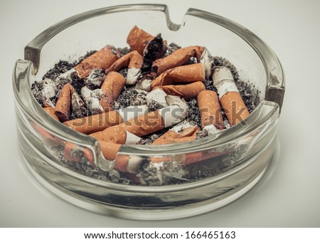 Cigarette butts in a glass ashtray vintage retro style background. - stock photo