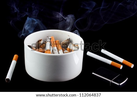 Cigarette butts in smoking ashtray, black background - stock photo