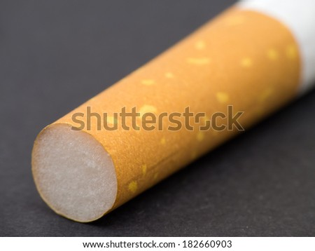 Cigarette filter macro on black textured background - stock photo