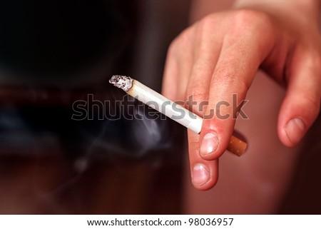 cigarette in a hand closeup - stock photo