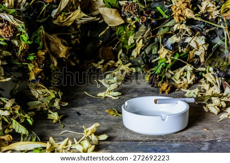 Cigarette in ashtray on grunge wood table - stock photo