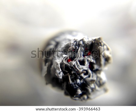 Cigarette or joint ash and ember, death skull face with eyes - stock photo