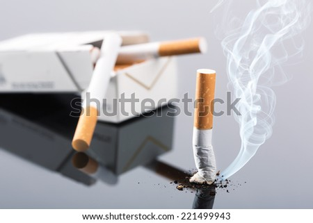 Cigarette package and butt on gray - stock photo