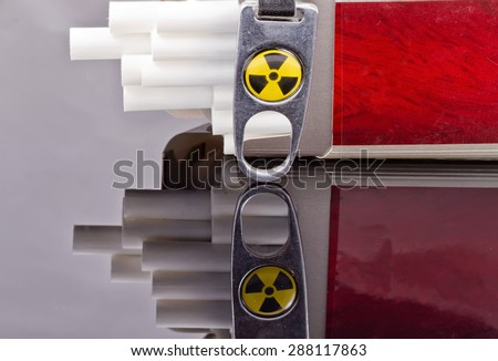 Cigarette protruding from the pack , lying close to the radioactive danger sign - stock photo