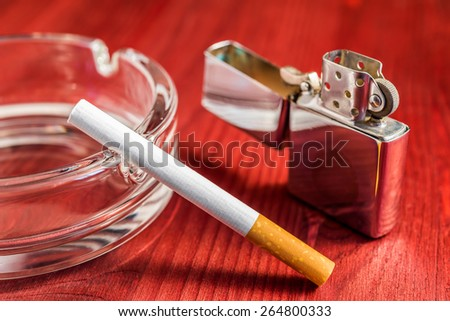 Cigarette with lighter and glass ashtray on the table. Focus on the cigarette - stock photo