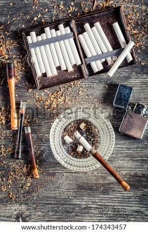 Cigarettes, ashtray and a smoking pipe - stock photo