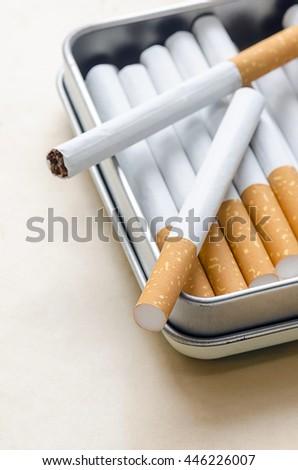 cigarettes silver cigarette case on brown paper background. - stock photo