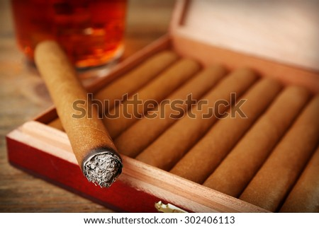 Cigars and burning one with cognac on wooden table, closeup - stock photo