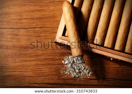 Cigars and burnt one with ash on wooden table, top view - stock photo