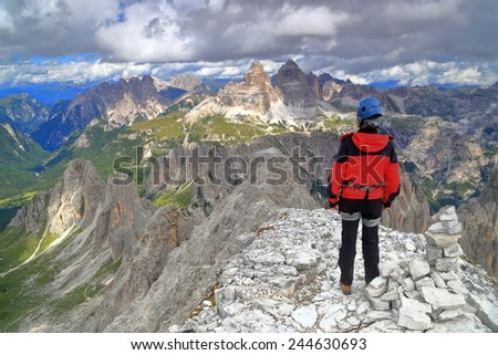 "Cima Nord Est summit and woman climber, via ferrata ""Merlone"",  Cadini di Misurina, Dolomite Alps, Italy - stock photo"