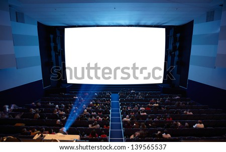 Cinema auditorium with people in chairs watching movie. Light of projector. High angle. Frontal view. Ready for adding your own picture. - stock photo
