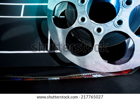 Cinema clapper and reels of film on the black background - stock photo