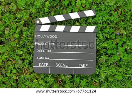 Cinema clapper board on green grass among flowering small purple flowers - stock photo