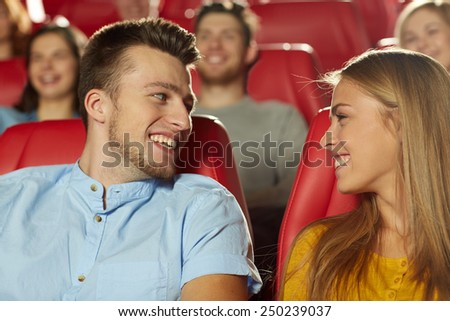 cinema, entertainment and people concept - happy friends watching movie and talking in theater - stock photo