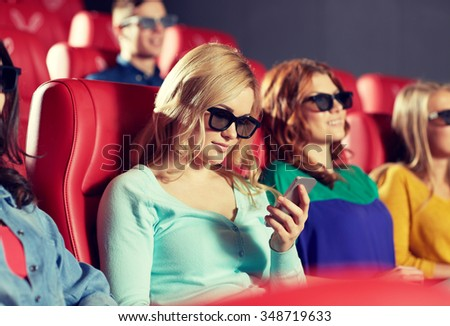 cinema, technology, entertainment and people concept - happy woman with 3d glasses and smartphone reading message in movie theater - stock photo