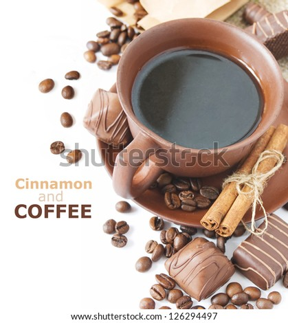 Cinnamon and coffee (Closeup shot of freshly prepared cup of coffee with cinnamon, coffee beans, chocolate candy and cakes isolated on white background with sample text) - stock photo