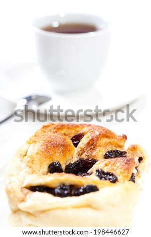 cinnamon bun with raisins and cup of tea, shallow dof - stock photo