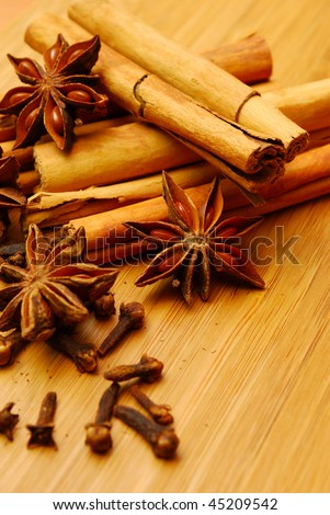 cinnamon cloves and star anise on a wooden board - stock photo