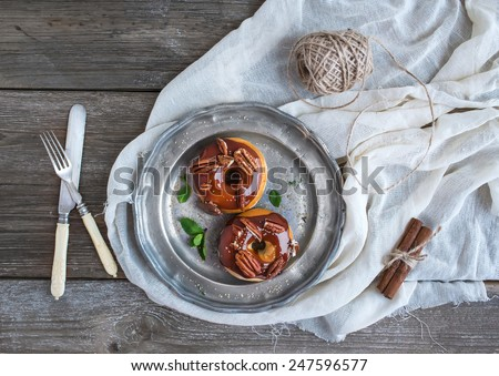 Cinnamon donuts with caramel icing and pecans served with fresh mint and cane sugar on a vintage metal plate over a white table cloth over a rustic wood background. Top view - stock photo