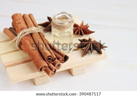 Cinnamon or anise essential oil. Cinnamon sticks, anise, bottle of aroma oil. - stock photo