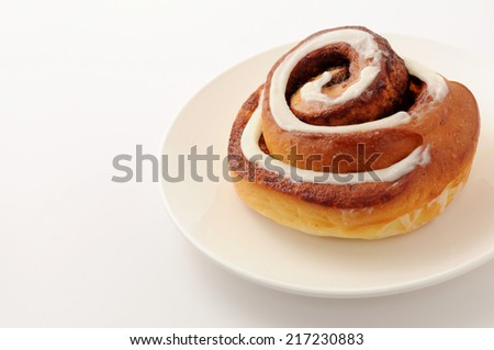 Cinnamon roll on plate isolated on white background  - stock photo