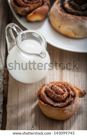 Cinnamon rolls and Bun with poppy seeds on a plate and small jugs of milk - stock photo