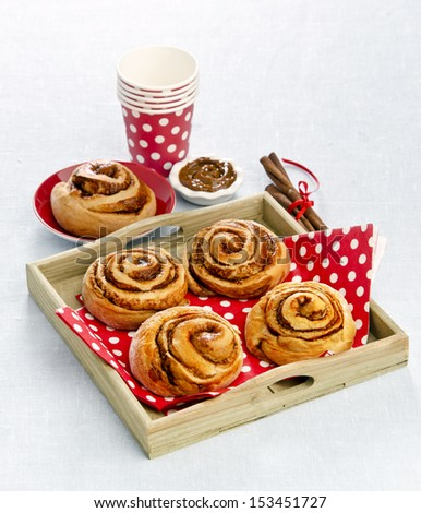 Cinnamon rolls and chocolate cream on a wooden tray - stock photo