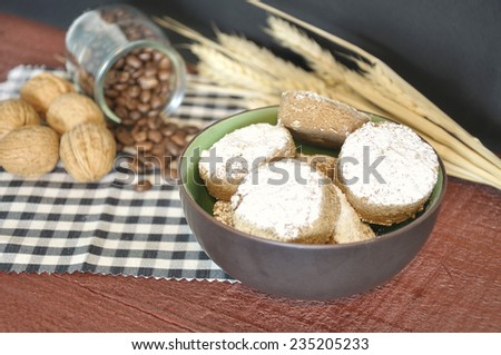 Cinnamon shortbread in a brown bowl and some ingredients like coffee, wheat and nuts on a wooden table on a black and white checkered napkin - stock photo