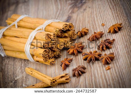 Cinnamon stick and star anise on wooden background - stock photo