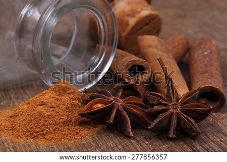 Cinnamon sticks and anice close up on wooden table - stock photo