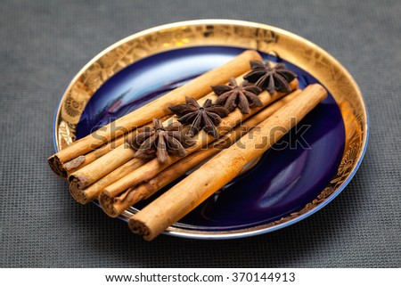 cinnamon sticks and anise on a beautiful blue saucer. Christmas ingredients - stock photo