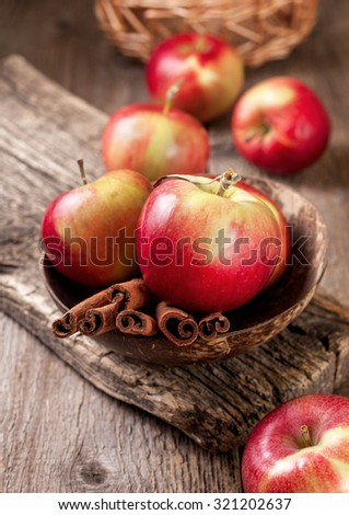 cinnamon sticks and apples on the old wooden background - stock photo