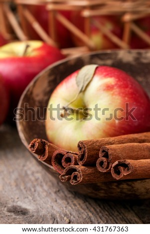 cinnamon sticks and apples on the old wooden background in rustic style - stock photo
