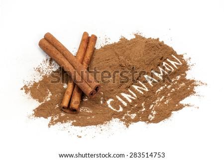"Cinnamon sticks and ""Cinnamon"" hand drawn in cinnamon powder on white background - stock photo"