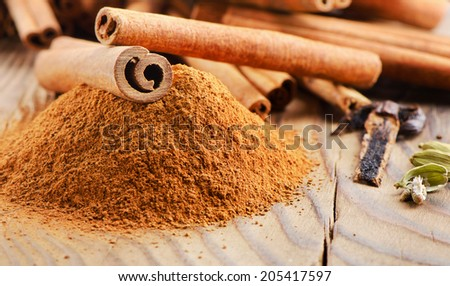 Cinnamon sticks and powder on wooden table. Selective focus - stock photo