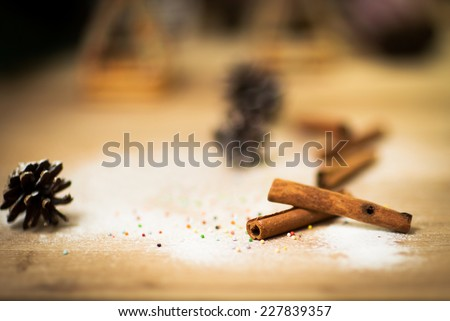 Cinnamon sticks on wood table with bundles of cinnamon in soft focus in background. Macro with extremely shallow dof. Selective focus limited to edges of closest sticks. - stock photo