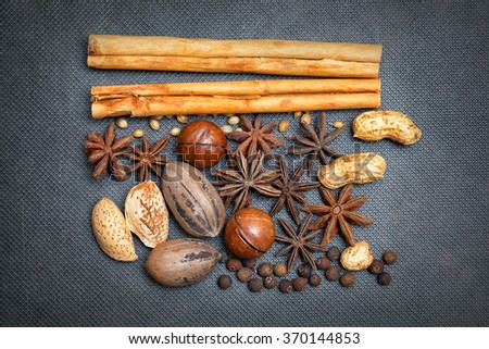 cinnamon sticks, pecans, almonds, macadamia, peanuts, star anise, black allspice, grains of sesame seeds. Creative design of nuts and spices - stock photo