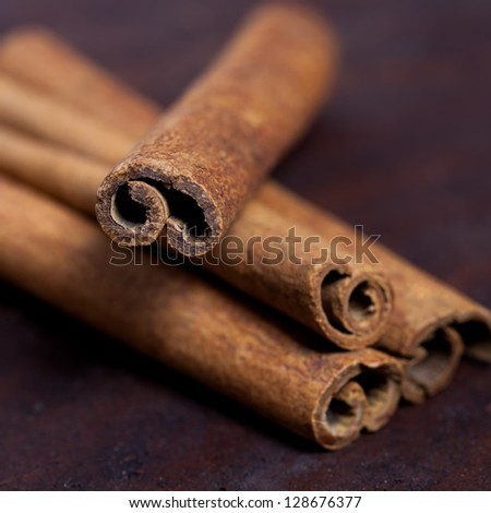 Cinnamon sticks, shot close-up on the table. Selective focus limited to edges of closest sticks - stock photo