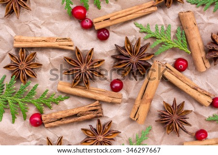 Cinnamon sticks, star anise, cranberry and branches of thuja on wrapping paper. Decorative background for Christmas and the New Year - stock photo
